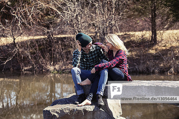 Happy couple talking while sitting on rock by lake