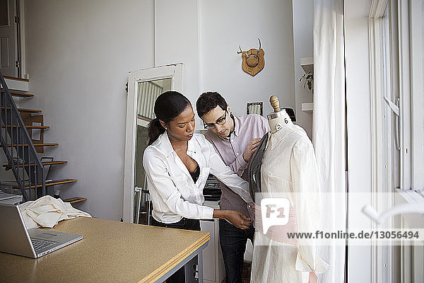 Fashion designers pinning dress on model in studio