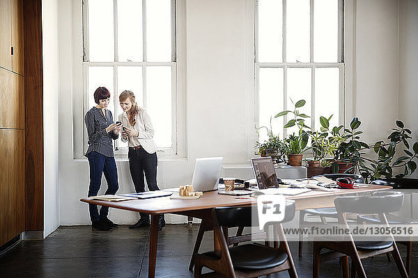 Businesswomen using phones while standing by window in board room