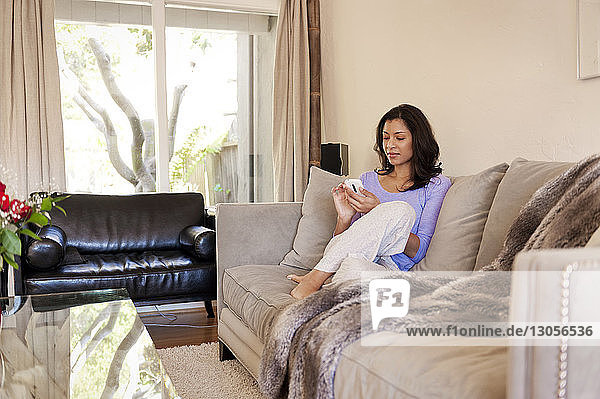 Woman using smart phone while relaxing on sofa at home