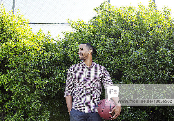 Happy young man holding basketball while standing against plants