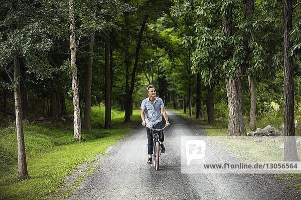 Glücklicher Mann radelt auf Straße im Wald
