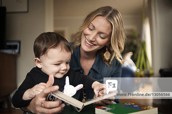 Mother showing picture book to baby boy at home