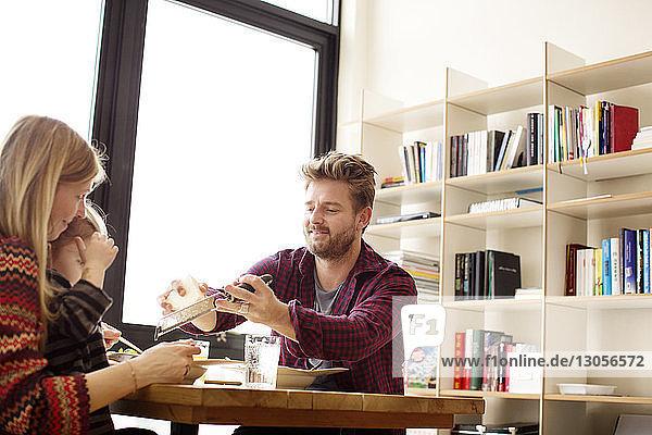Mann reibt Käse auf dem Teller  während er mit der Familie bei Tisch isst