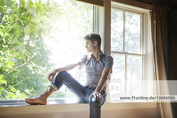 Thoughtful man sitting on window at home