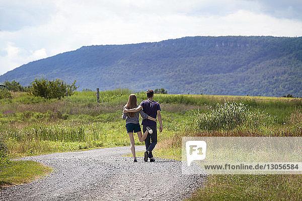 Rückansicht eines Paares  das auf einer Schotterstraße gegen einen Berg steht