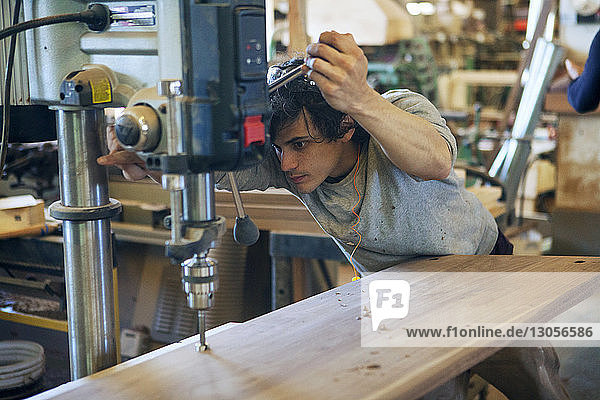 Male carpenter using machinery on wooden plank at workshop