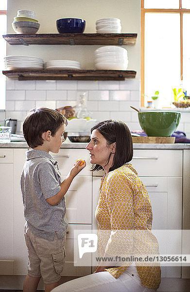 Boy talking to mother in kitchen