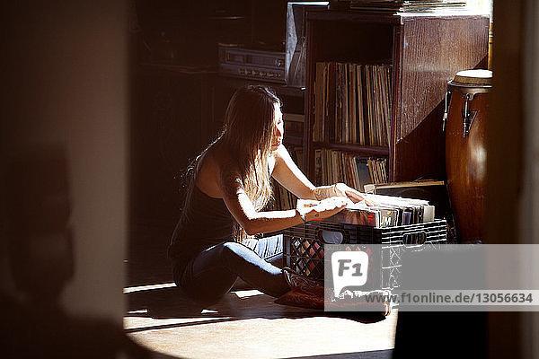 Frau durchsucht Aufzeichnungen  während sie zu Hause sitzt