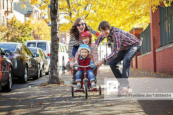 Happy family enjoying skateboard and tricycle on footpath
