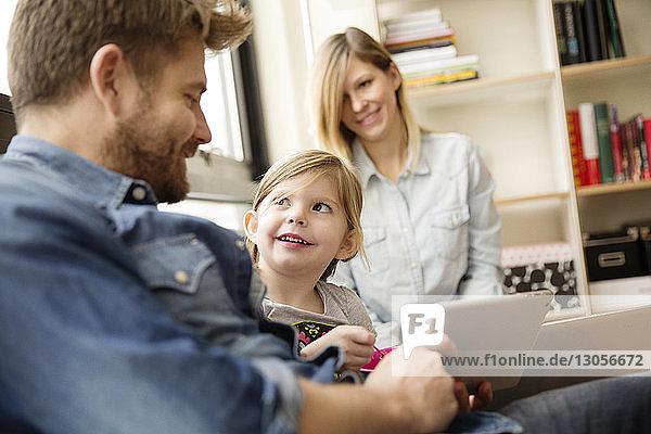 Mädchen sieht Vater mit digitalem Tablet und Frau im Hintergrund