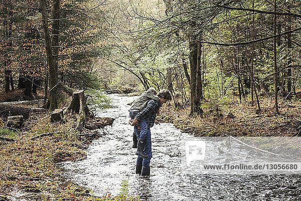 Seitenansicht eines Vaters  der seinen Sohn beim Überqueren eines Flusses huckepack nimmt
