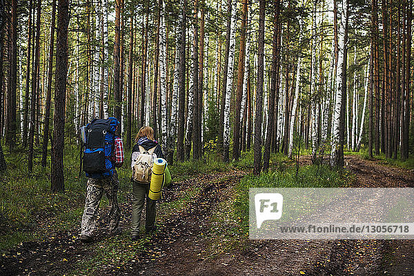Rear view of man and woman carrying backpack while walking in forest