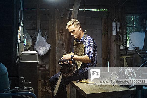 Mann hält Kettensäge  während er in der Werkstatt auf dem Tisch sitzt