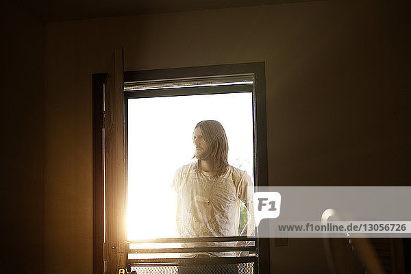 Man looking away while standing by window