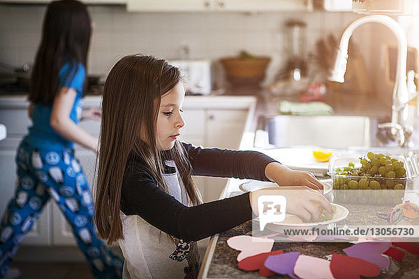 Girl taking grapes at kitchen counter by sister in home