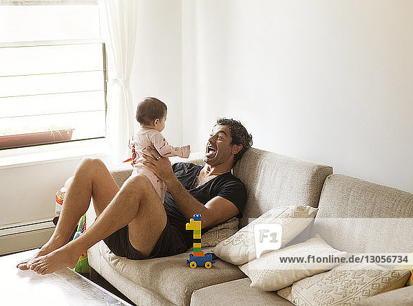 Father playing with daughter while sitting on sofa at home