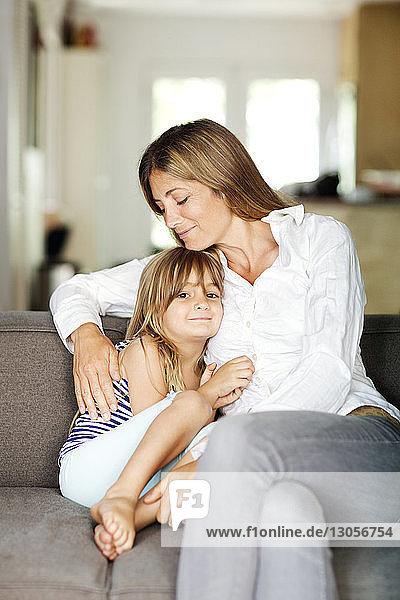 Lächelndes Mädchen sitzt mit der Mutter auf dem Sofa