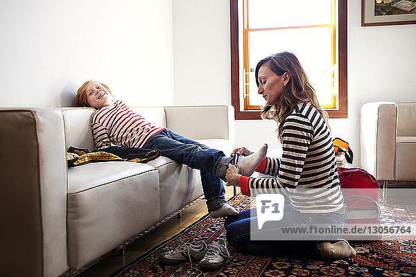 Mutter hilft Sohn beim Tragen von Socken zu Hause