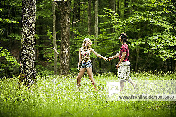 Couple holding hands while walking on grassy filed