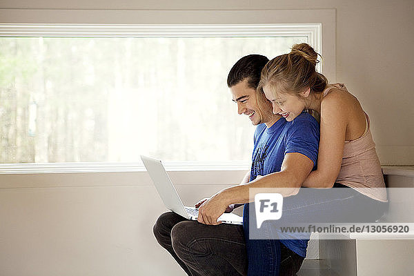 Happy couple using laptop computer while sitting on steps at home