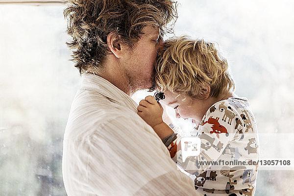 Seitenansicht eines Vaters  der die Stirn seines Sohnes küsst