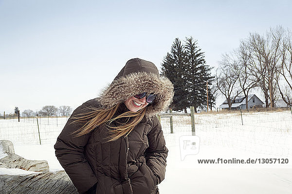 Cheerful woman standing on snowy field against clear sky