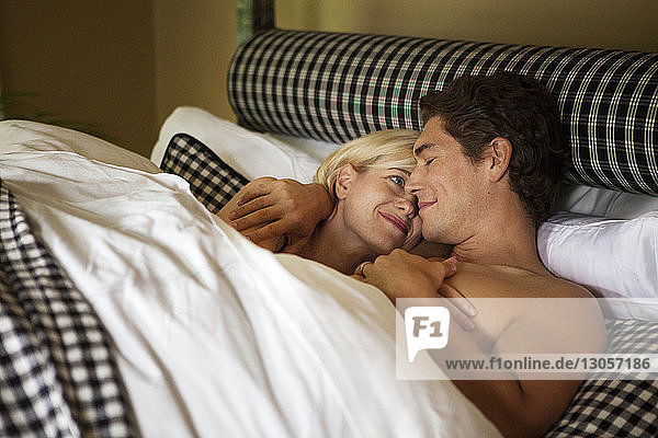 Happy couple sleeping on bed at home