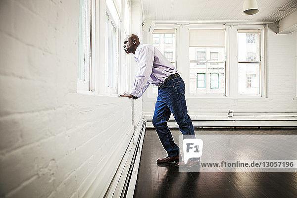 Geschäftsmann schaut durch ein Fenster im Büro