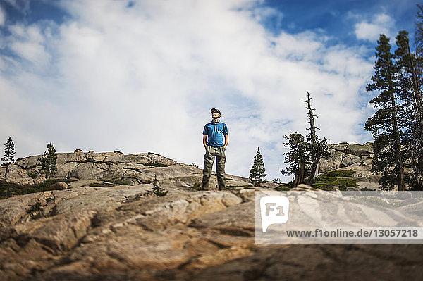 Niedrigwinkelansicht eines Mannes  der auf einer Felsformation gegen den Himmel steht