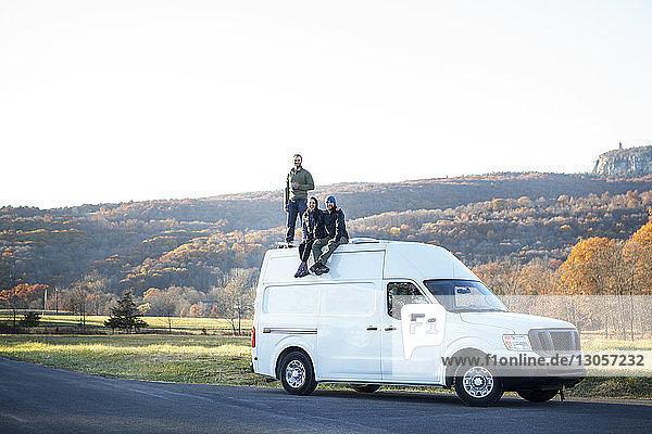 Freunde auf Wohnmobil gegen klaren Himmel