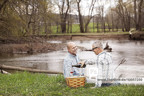 Schwules Paar trinkt Rotwein  während es am See sitzt