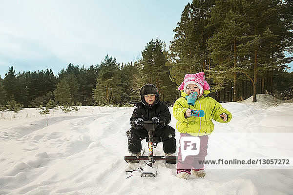 Boy sitting on sledge while sister walking on snow covered field