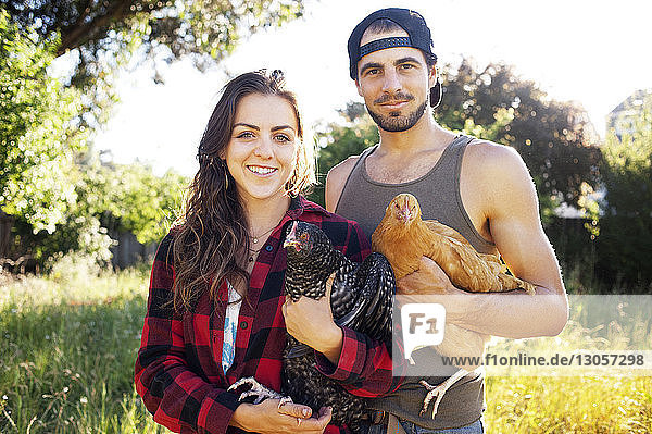 Portrait of couple holding chickens while standing on field