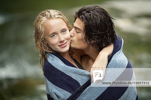 Portrait of affectionate couple wrapped in towel