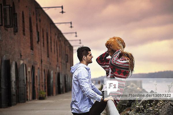 Mann betrachtet Freundin mit Pelzmütze bei Sonnenuntergang