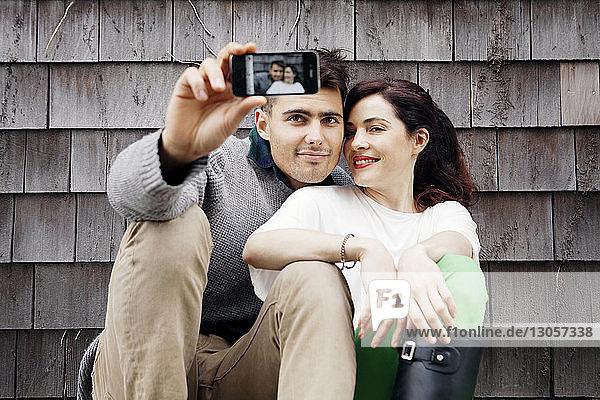 Mann und Frau  die sich an einer Holzwand sitzend Selbsthilfe nehmen