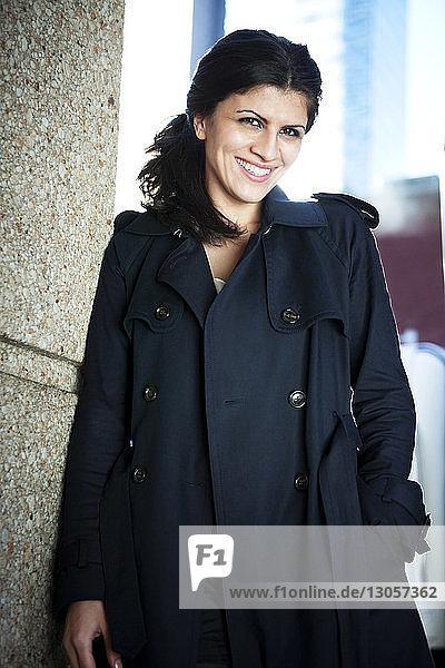 Porträt einer glücklichen Frau in langem Mantel  die an der Wand steht