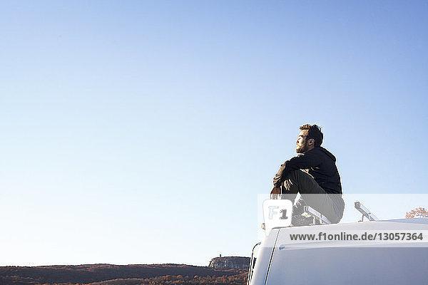 Seitenansicht eines auf einem Wohnmobil sitzenden Mannes vor klarem Himmel