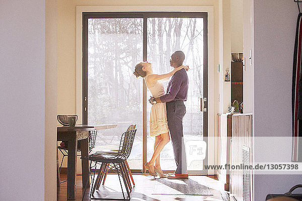 Side view of couple standing by window at home