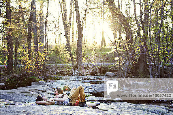 Happy couple talking while lying on rock at forest