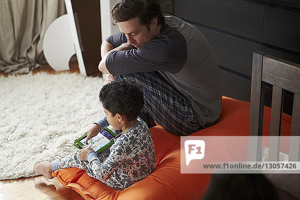 Boy using tablet while sitting with father at home