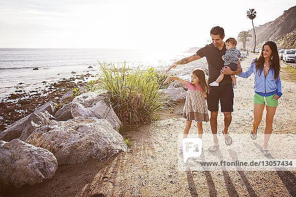 Glückliche Familie geht am Strand gegen den Himmel