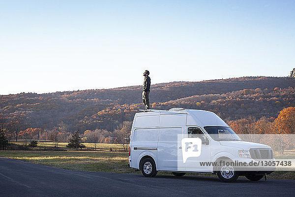 Mann steht auf Wohnmobil gegen klaren Himmel