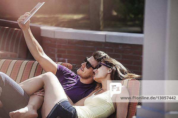 Glückliches Paar beim Selbermachen auf dem Sofa im Hinterhof