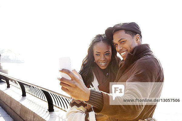 Smiling couple clicking selfie with smart phone at railing against sea