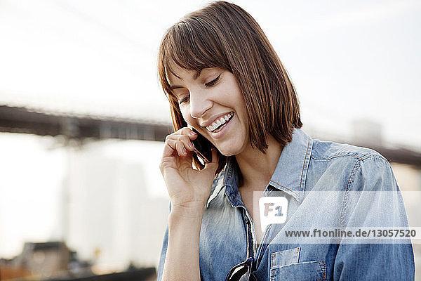 Nahaufnahme einer glücklichen Frau bei der Benutzung eines Mobiltelefons