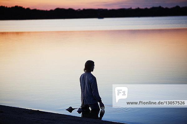 Rear view of man kneeling at shore