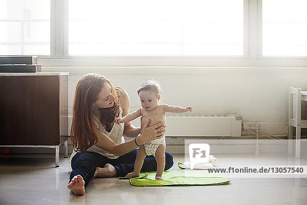 Mother assisting baby girl to walk at home