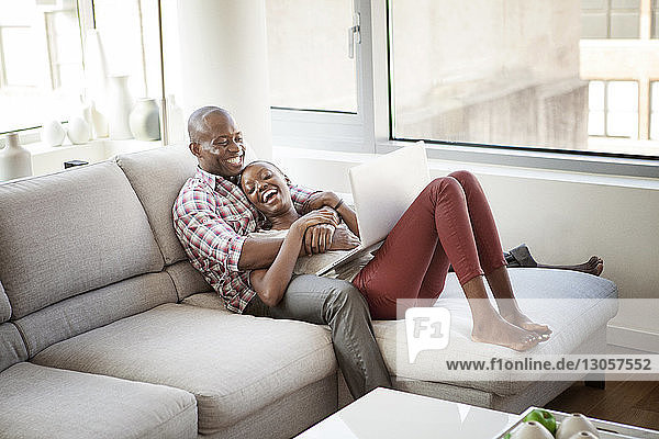 Cheerful couple using laptop computer while sitting on sofa at home